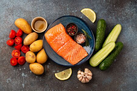 Raw salmon fish fillet, fresh vegetables, herbs - ingredients for cooking healthy meal. Natural clean organic healthy food selection on concrete background, dieting and nutrition concept. Top view Stok Fotoğraf