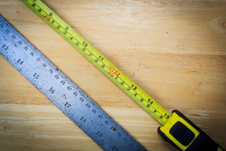 tape measure and ruler on wood background photo