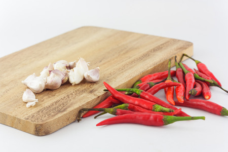 trencher: group of red chili and garlic with chopping block in white background