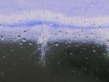 rain droplet on car window on green grass background