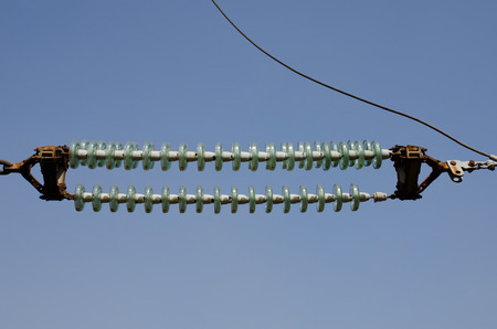 amperage: High-voltage Transmission Insulators against the blue sky Stock Photo