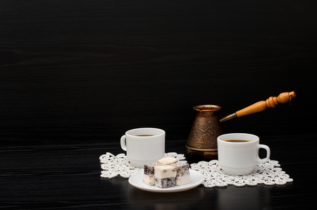 Two cups of coffee on white napkins, pots and Turkish sweets on a black background. Space for text