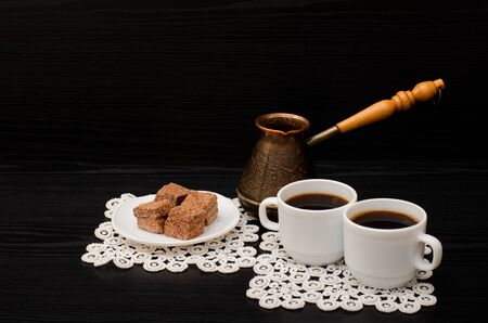 turkish dessert: Two cups of coffee on the lace napkins, pots and chocolate turkish dessert on a black background