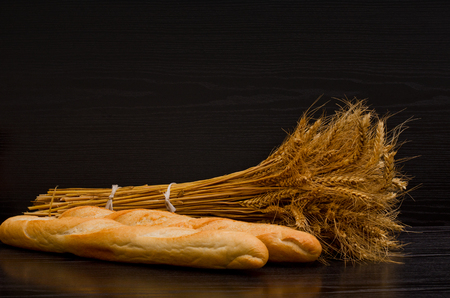 sheaf: Two white loaf and a sheaf on a black background, with space for text
