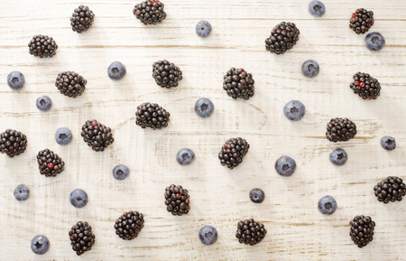 fill: Blueberries and blackberries fill light wooden background Stock Photo