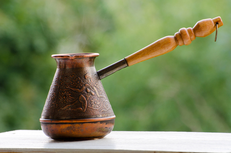 cezve: Copper Cezve with hot coffee on a windowsill, blurred green background Stock Photo