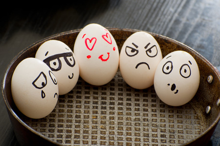 resentment: Whole eggs in a frying pan with different emotions Stock Photo