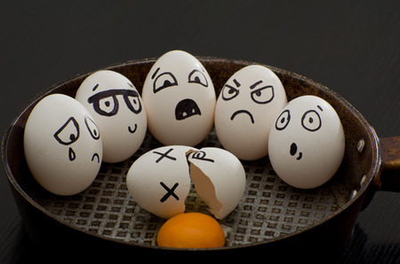 broken eggs: Broken egg in a pan surrounded by whole eggs with different emotions