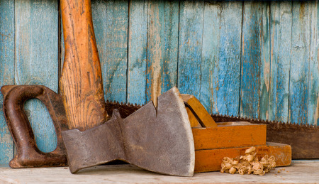 Carpenter tools: ax, planer and saw on the background of the old wooden walls