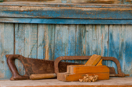 Planer, hacksaw and a saw on an old wooden background, chips Stock Photo