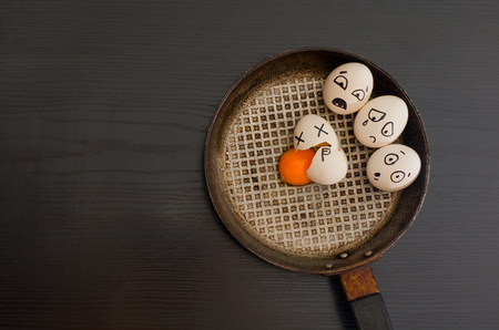 broken egg: Eggs with the drawn emotions, broken egg in the center of the pan, black table