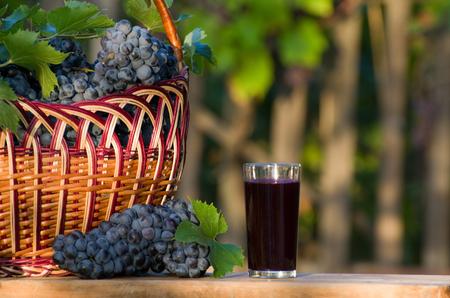 ブドウ枝編み細工品バスケット付きブドウ ジュース、バック グラウンドで庭のガラス
