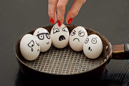 resentment: Eggs with painted emotions in a frying pan, a female hand takes one of them Stock Photo