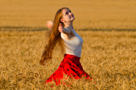 Girl in red skirt whirling in wheat field arms spread out Stock Photo