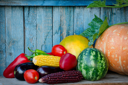 Autumn still life of vegetables. Corn, eggplant, squash, peppers, watermelon in the old background. Space for text Stock Photo