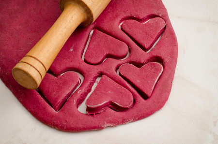 Red beet dough with cut out hearts, rolling pin, top view close up