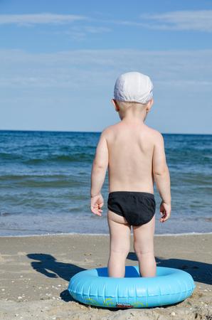 Kleiner Junge auf der Küste mit einem Swimming-Kreis ist mit dem Rücken