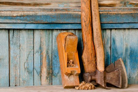 Old tools. Axe and plane on a vintage wooden background, with space for text