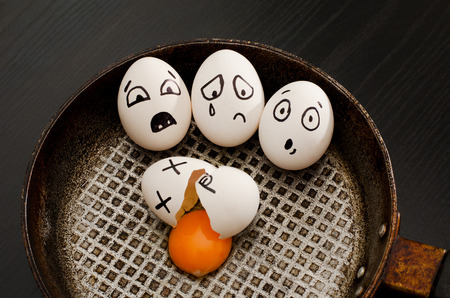 resentment: Top view of a broken egg, and egg with frightened faces in a frying pan. food concept