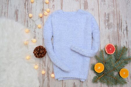 warm things: Warm blue sweater on a wooden background. Spruce twigs, oranges and festive garland. Fashion concept