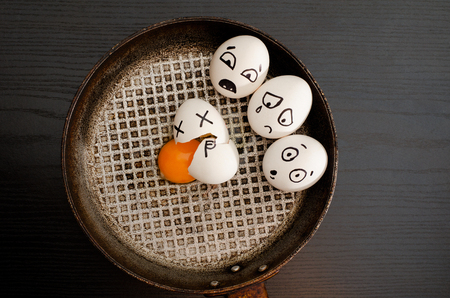 resentment: Three eggs painted with emotions, broken egg in the center of the pan, black table, space for text