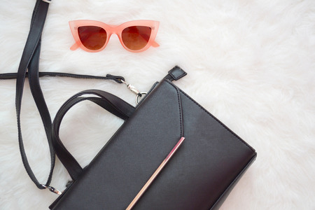 view an elegant wardrobe: Fashion concept. Black handbag and pink glasses on a white background. top view