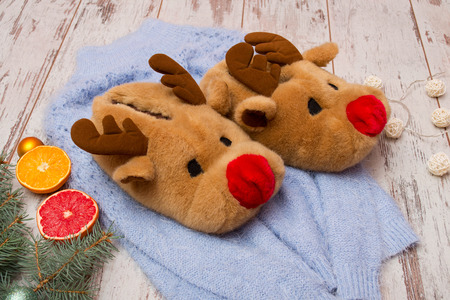 stuff toy: Soft slippers-deer on a blue sweater, spruce branch, citrus fruits and a garland on a wooden background Stock Photo