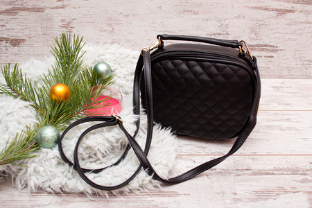 Small black female handbag on a wooden background, fir branch with ornaments, candle. fashion concept