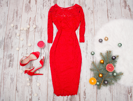fir branch: Red elegant lace dress, red shoes on a wooden background, fir branch with ornaments and citrus. fashion concept