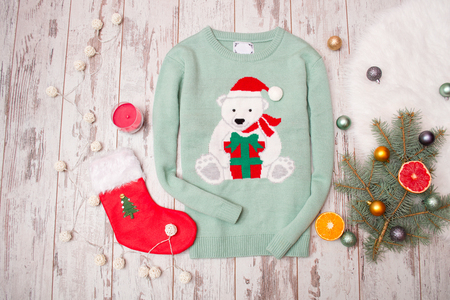 warm things: Green sweater with a bear on a wooden background. Fir-tree branch with Christmas decorations, stocking, gift