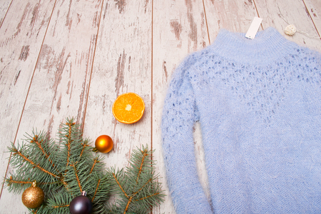 warm things: Christmas concept blue knitted sweater with a tag, spruce branch with ornaments, orange. Space for text