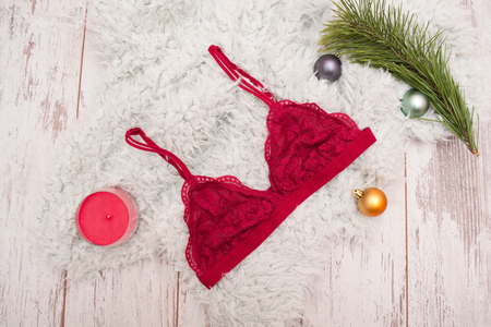 bra top: Fashionable concept, burgundy lace bra with artificial fur, candle and spruce branch. Wooden background, top view