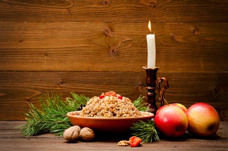 fir branch: Traditional Christmas treat of the Slavs on Christmas eve kutia. Fir branch, apples, candle on wooden background. Place for text