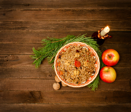 slavs: Top view of a dish of traditional Christmas dish Slavs - kutia. Wooden background spruce branch, apples. Space for text