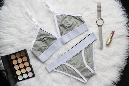 Gray white linen set for sports on a white fur. Watches, lipstick, eye shadow. Fashionable concept, top view