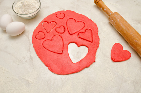 Red dough with a rolling pin and cut out hearts on a white table, close-up Stock Photo