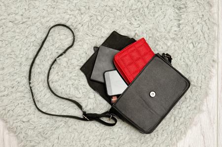 オープン ブラック ハンドバッグ、赤い財布、携帯電話、それの口紅。灰色の毛皮の背景、平面図。ファッションの概念 写真素材