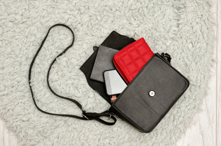 Open black handbag, red purse, mobile phone and lipstick in it. Grey fur background, top view. fashion concept