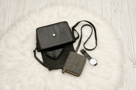 view an elegant wardrobe: Open black bag with a spill out of her phone, a gray purse and a watch. The white fur on background, top view. fashion concept