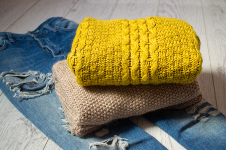 warm things: Two knitted sweaters on torn jeans, a wooden background. Fashionable concept, side view