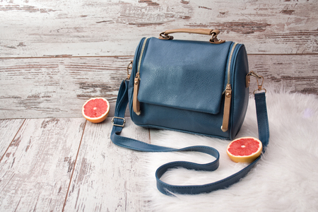 Blue bag with zippers on white fur, half a grapefruit, a light wooden background