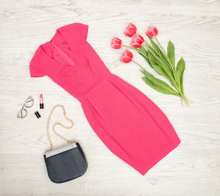 Fashion concept. Crimson dress, handbag, lipstick, glasses and pink tulips. Top view, light wood background Stock Photo