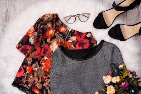 Blouse in flowers and gray on white fur, glasses, shoes and a bouquet of flowers. Fashionable concept, top view Stock Photo