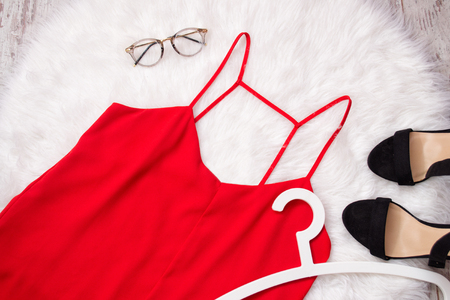 Red chiffon T-shirt, glasses and shoes on white fur. Fashionable concept, top view