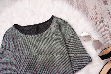 Blouse of metallic color and glasses on white fur. Fashionable concept, top view