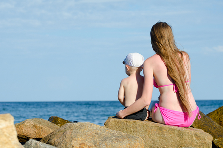 Mother and son sitting on a rock on the seashore and looking into the distance