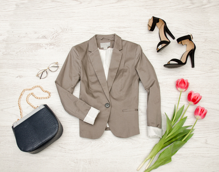 stuff: Fashion concept. Gray jacket, handbag, sunglasses, shoes and pink tulips. Top view, light wood background
