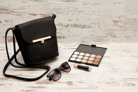 stuff: Little black ladies handbag, sunglasses, lipstick and eyeshadows on wooden background. fashion concept Stock Photo