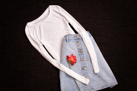 stuff: White blouse and jeans skirt, rose. Fashionable concept, top view
