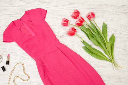 Fashion concept. Crimson dress, lipstick and pink tulips. Top view, light wood background